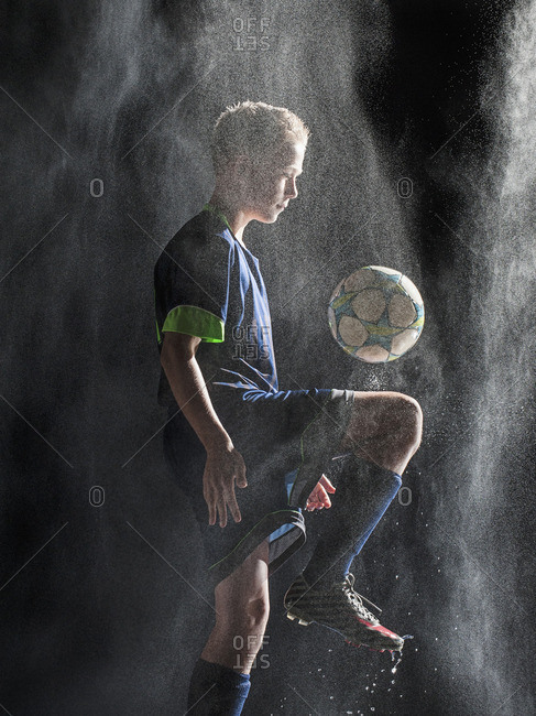 Caucasian soccer player kicking ball in rain