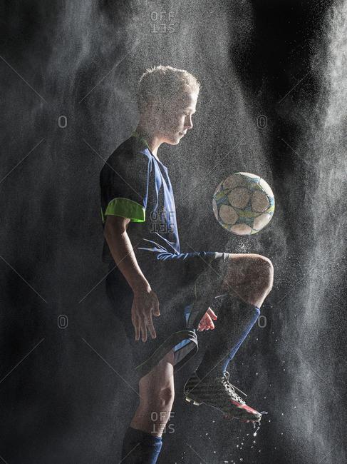 Caucasian soccer player kicking ball in rain