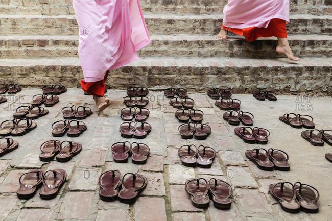 Nuns leaving sandals outside temple steps