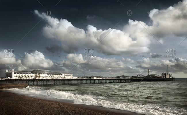 Clouds over boardwalk and beach, Brighton, Sussex, England