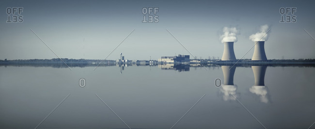 Smoke stacks and factory reflected in still lake
