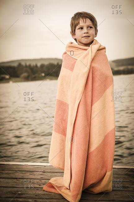 Caucasian boy wrapped in towel on wooden dock