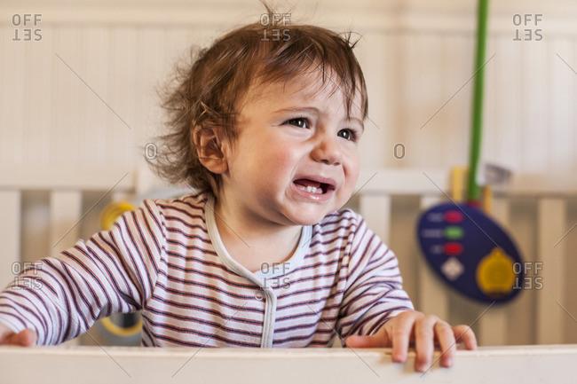 Hispanic toddler crying in crib