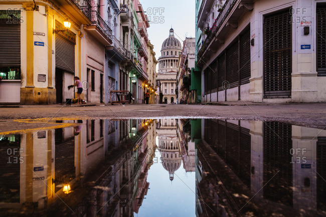 Ornate city building reflected in puddle, Havana, Cuba
