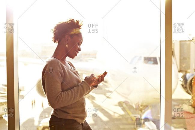 Black woman using cell phone in airport