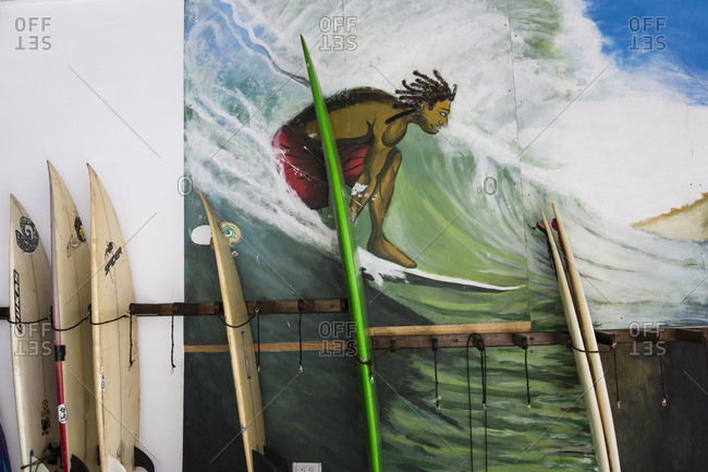 Taiwan - May 25, 2016: Surfboards propped by a wall with painting of a man surfing
