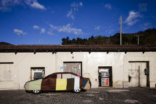 Antigua, Guatemala - February 8, 2016: Car covered with tarp in front of a gas station