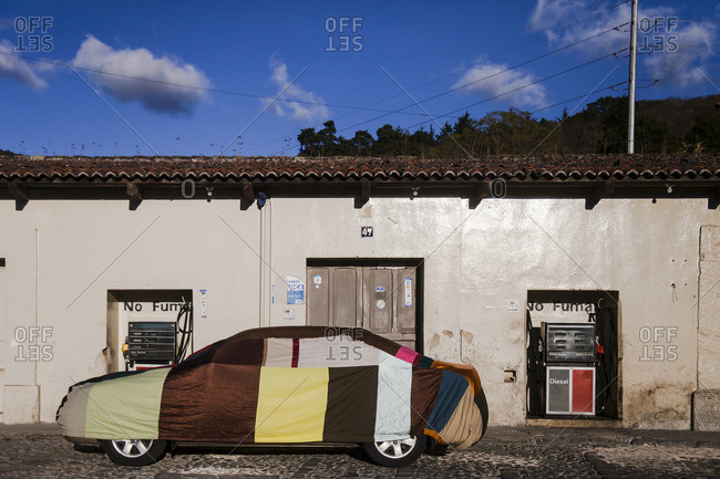 Antigua, Guatemala - February 8, 2016: Car covered with tarp in front of a gas station in Antigua