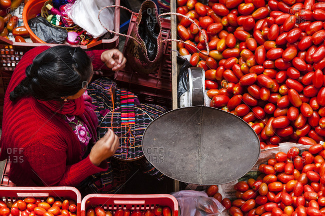 Woman stitching a colorful cloth while selling tomatoes at a market in Chichicastenango, Guatemala