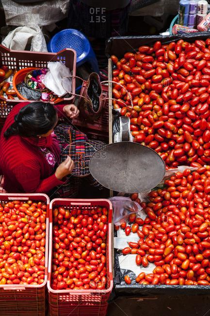 Chichicastenango, Guatemala - February 11, 2016: Woman stitching a colorful cloth while selling tomatoes at a market