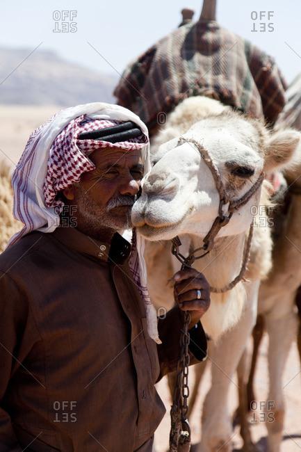 Wadi Rum, Jordan - June 1, 2015: Man kissing his camel in the Wadi Rum desert