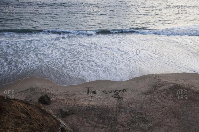 "Girls writing ""Te quiero!"" in the sand on a beach in San Agustinillo, Oaxaca, Mexico"