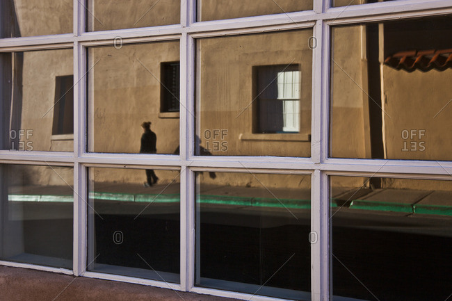 Window with reflection of building and person in Santa Fe, New Mexico
