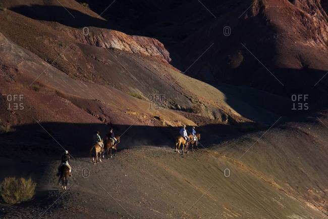 People riding horseback through hills in San Juan, Puerto Rico
