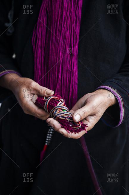 Man holding colorful strings, Sa Pa, Vietnam