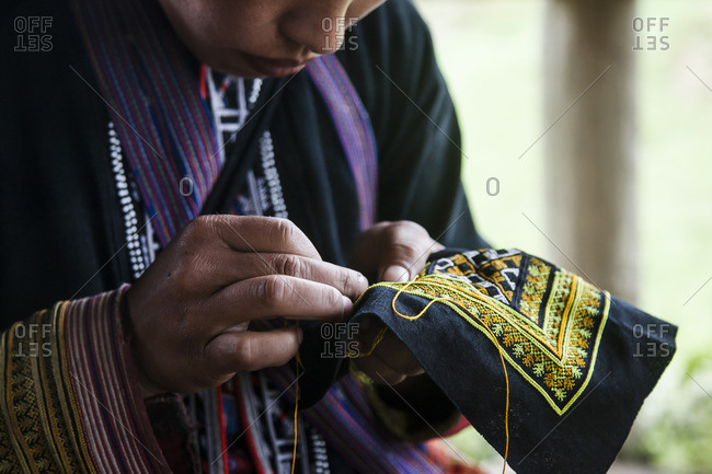 Man stitching a colorful cloth in Sa Pa, Vietnam