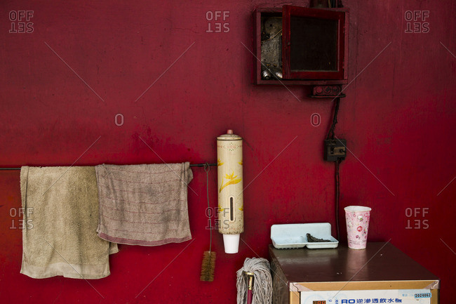 Red wall with dirty hanging hand towels, Tainan, Taiwan