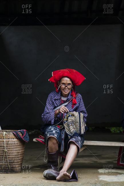 Sa Pa, Vietnam - September 27, 2008: Woman sitting on a bench stitching a fabric in Sa Pa, Vietnam