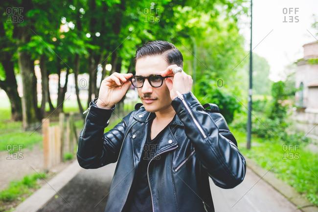 Man adjusting spectacles in park