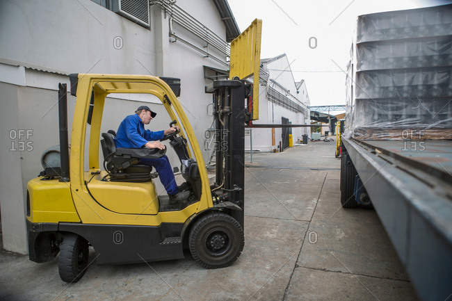 Forklift driver loading pallet onto truck at packaging factory