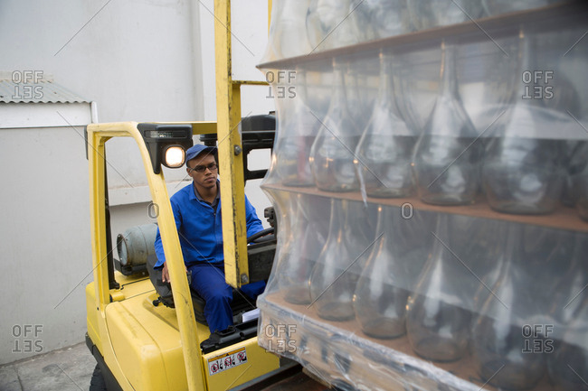 Forklift driver loading pallets at packaging factory
