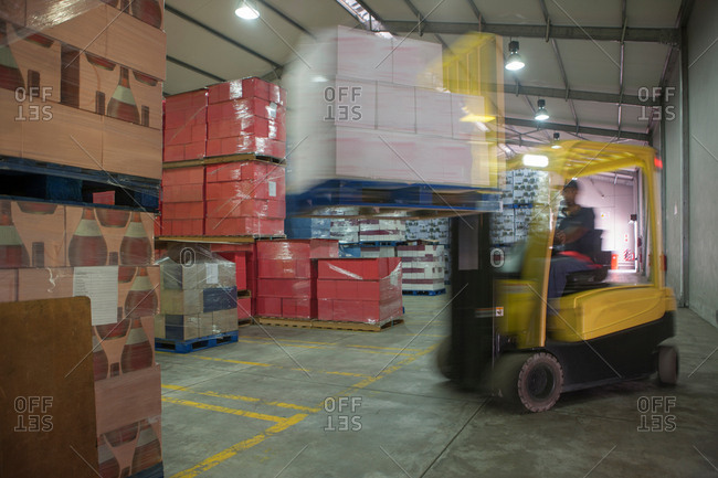 Forklift truck drivers loading pallet at packaging factory warehouse