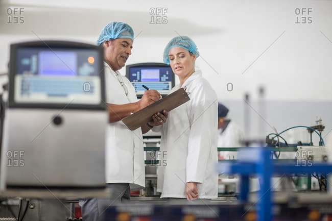 Lab technicians checking equipment at packaging factory lab