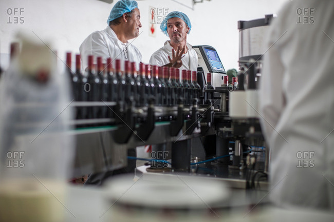 Factory workers on production line of wine bottling plant