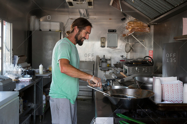 Man cooking food in fast food trailer