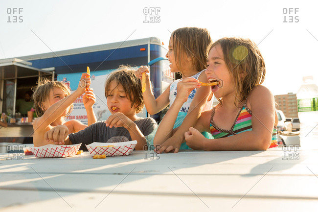 Group of children eating fast food beside fast food trailer
