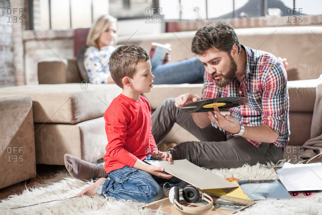 Father showing vinyl record to son at home