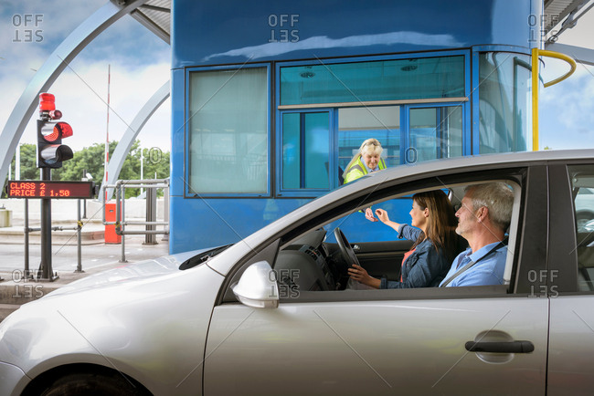 Driver in car paying at toll booth at bridge