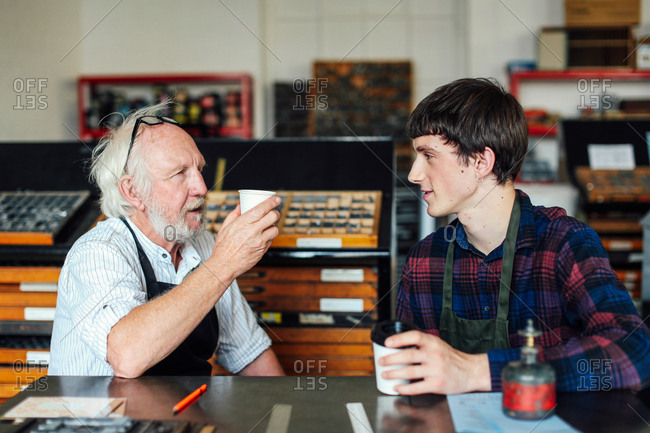 Senior craftsman drinking coffee and chatting to young craftsman in book arts workshop
