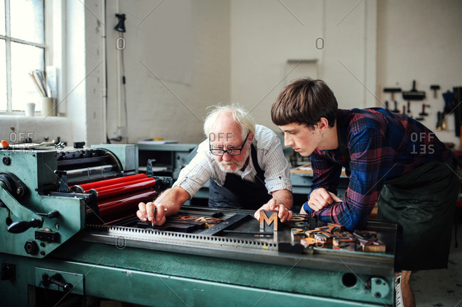 Senior craftsman teaching young craftsman to use letterpress machine in book arts workshop