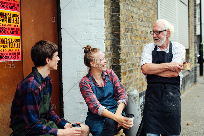 Senior craftsman chatting and laughing with young craftswoman and craftsman outside print workshop