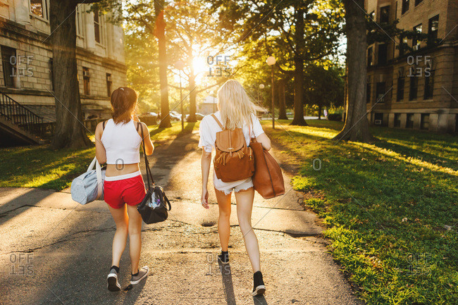 Women on walkway heading towards sunset, Boston, MA, USA
