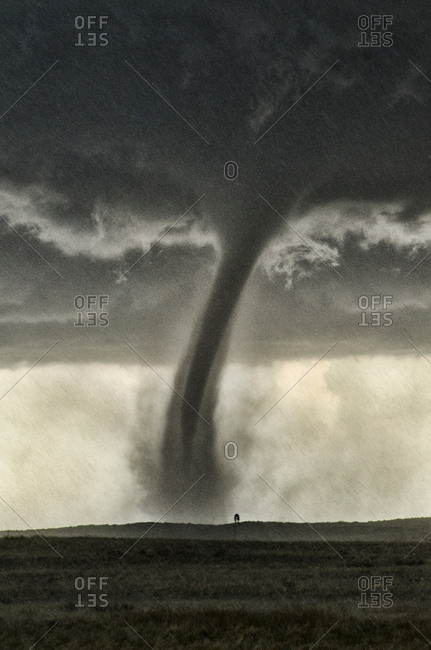 A back-lit tornado spinning up dust in rain and hail, with windmill in distance, Wray, Colorado