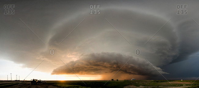 Panoramic view of a tornado-producing supercell thunderstorm spinning over ranch land at sunset near Leoti, Kansas