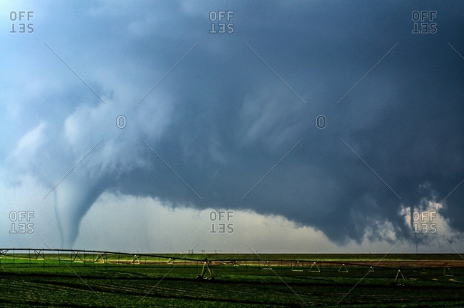 A supercell thunderstorm produces two tornadoes at once in a farm field south of Dodge City, Kansas