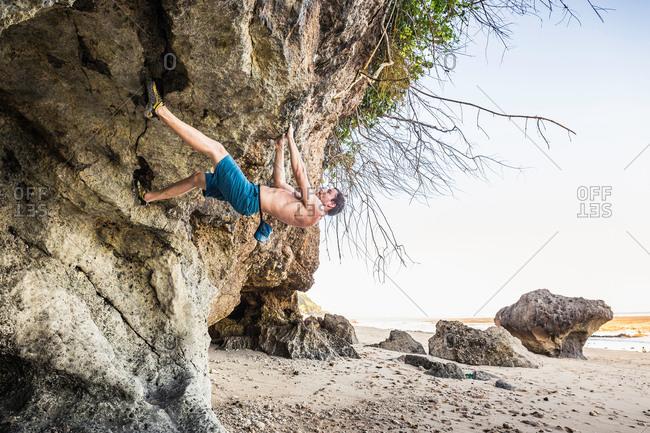Male free climber climbing rock overhang on Pandawa Beach, Bali, Indonesia