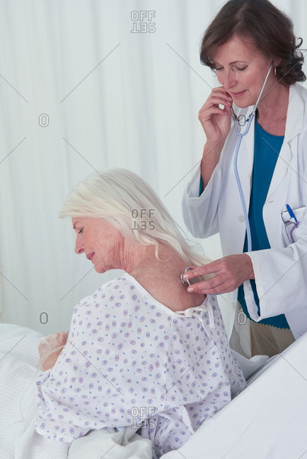 Female doctor listening to senior female patient back with stethoscope