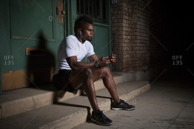 Young man with mohawk, sitting on steps at night, wearing earphones