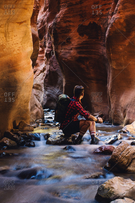 Male hiker sitting in cave on river rock, Zion National Park, Utah, USA