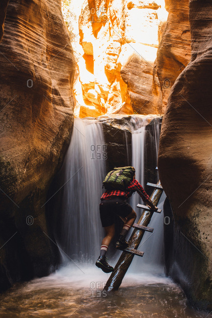 Male hiker climbing cave ladders, Zion National Park, Utah, USA