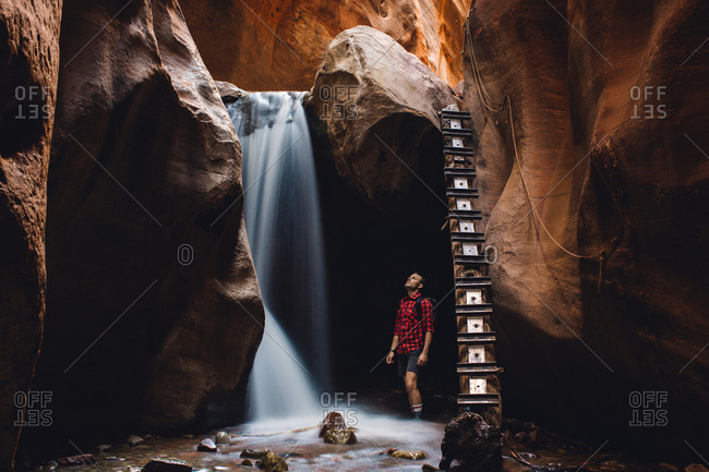Male hiker looking up at waterfall in cave, Zion National Park, Utah, USA