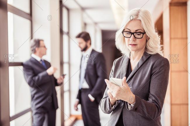 Businesswoman reading smartphone update in office corridor