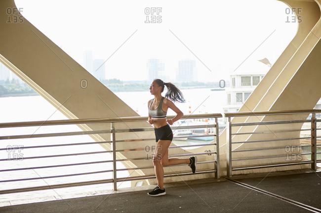 Woman jogging on elevated walkway, South Bund, Shanghai, China