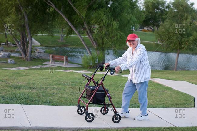 Senior woman walking outdoors with walking frame
