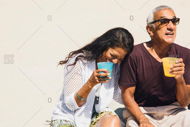 Senior couple sitting on beach, laughing, holding cold drinks, Long Beach, California, USA
