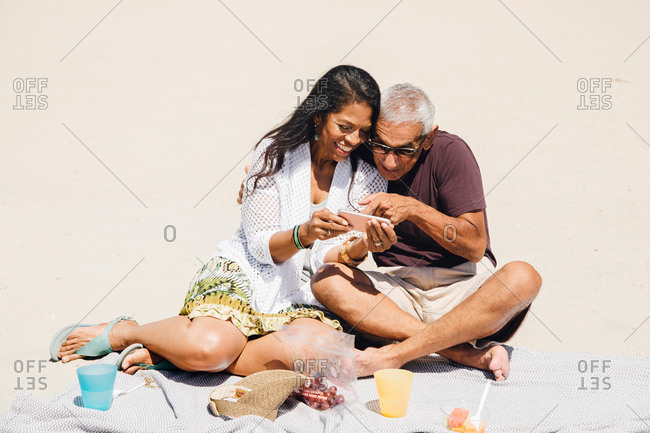 Senior couple sitting having picnic on beach, looking at smartphone, Long Beach, California, USA